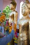 Люди положили листовое золото на золото Будду стоковые изображения