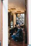 Люди получая стрижки внутри парикмахерскаи экипажа Ottoman турецкой, Лондона, Великобритании стоковая фотография rf