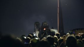 Люди поя и моля во время огня собора Нотр-Дам видеоматериал