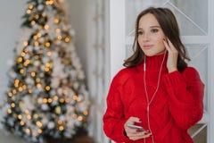 Люди, праздники и концепция технологии Милая женщина использует мобильный телефон и наушники для слушая музыки, стоят дома против стоковое изображение rf
