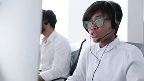 Люди работают в центре контакта Женщина в деятельности шлемофона акции видеоматериалы