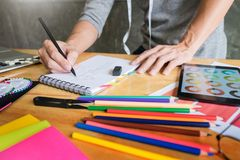 люди работая как эскизы чертежа модельера для одежд внутри Стоковые Изображения
