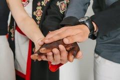 Люди различных национальностей и вероисповеданий держат руки Концепция приятельства среди людей Концепция  Стоковые Фотографии RF