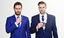 Люди регулируя деловые костюмы Уверенный в их стиле Бизнесмены выбирают официально одежду Каждая деталь имеет значение стоковое фото