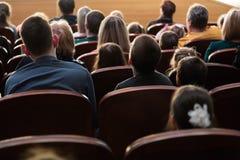 Люди, родители с детьми в аудитории наблюдая ` s детей показывают Распродано Стрельба от задней части Стоковое фото RF