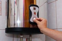 Люди рук взрослые установили температуру воды в электрическом котле Закройте вверх мужских рук поворачивая ручку электрического Стоковое Фото
