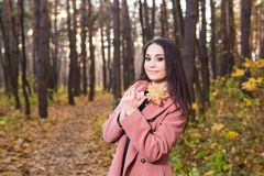 Люди, сезон и концепция стиля - красивая молодая женщина усмехаясь в парке осени стоковые фотографии rf