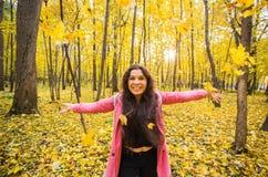 Люди, сезон и концепция эмоции - молодая милая усмехаясь женщина имеет потеху на парке осени стоковые изображения