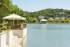 Люди сидят в кафе лета на береге озера Abrau в деревне курорта - центре туризма вина лето дня солнечное Стоковые Изображения RF
