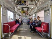 Люди сидя в метро в Токио, Японии МЛАДШЕГО стоковое фото