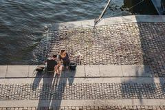 Люди сидя на обваловке реки Влтавы в Праге, чехии стоковое фото rf