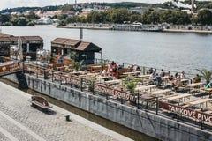 Люди сидя на таблицах кафа на реке Влтавы в Праге, чехии стоковое изображение