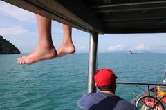 Люди сидя на шлюпке и путешествуя вокруг острова Стоковые Фотографии RF