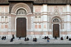 Люди сидя перед Сан Petronio Собором Базиликой di Сан Petronio в болонья стоковые изображения rf