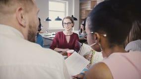 Люди смешанной гонки читая деловые документы Счастливые молодые работники прочитали договоры подряда на конторском персонале встр акции видеоматериалы