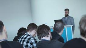 Люди смотрят по мере того как диктор говорит интересную речь на бизнес-конференции сток-видео