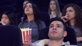 Люди смотрят серьезный фильм на кинотеатре стоковое изображение