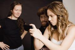 Люди смотря изображения на smartphone Стоковые Изображения RF