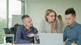 Люди собирают используя компьтер-книжку в современном startup офисе Стоковые Фото