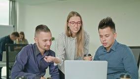 Люди собирают используя компьтер-книжку в современном startup офисе Стоковое Фото