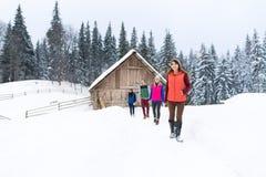 Люди собирают около деревянного коттеджа курорта снега зимы загородного дома Стоковые Фото