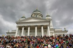 Люди собраны на шагах собора Хельсинки для ожидания гей-парада начать стоковое фото