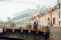 Люди стоят на мосте над каналом в Санкт-Петербурге стоковые фото