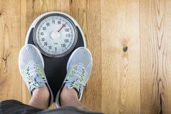 Люди стоя дальше весят масштабы на спортзале Измерение талии рулеткой concept healthy lifestyle стоковые фото