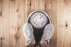 Люди стоя дальше весят масштабы на спортзале Измерение талии рулеткой concept healthy lifestyle стоковые изображения