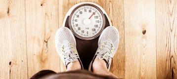 Люди стоя дальше весят масштабы на спортзале Измерение талии рулеткой concept healthy lifestyle стоковая фотография rf