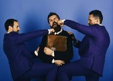 Люди с бородой и серьезные стороны пробивают человека с портфелем Стоковые Изображения RF