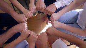 Люди с сжатыми кулаками делают круг и после этого аплодируют одину другого сидя на стульях на терапии группы акции видеоматериалы