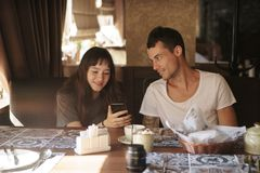 Люди, технология, образ жизни и концепция датировка - счастливая пара с кофе и smoothie smartphone выпивая на кафе стоковые фото