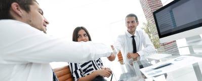 Люди тряся руки и усмехаясь пока сидящ на столе Стоковая Фотография