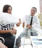 Люди тряся руки и усмехаясь пока сидящ на столе Стоковые Фотографии RF