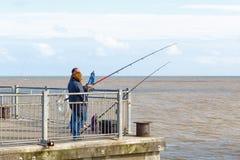 Люди удя с рыболовными удочками на пристани Southwold в Великобритании стоковые фотографии rf