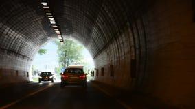 Люди управляя автомобилем на проведенной дороге горой в тоннеле автомобиля идут к городу Meran видеоматериал