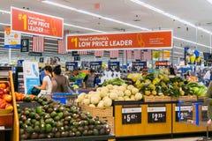 Люди ходя по магазинам на Walmart для свежей продукции стоковые изображения