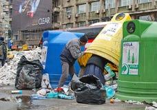 Люди Gypasy крадя пластиковые бутылки от пластиковых выборочных собирая контейнеров на улице в Бухаресте, Румынии стоковые фото