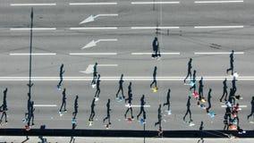 Люди jog вдоль серой дороги с белыми маркировкой и стрелками акции видеоматериалы