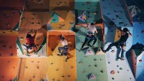 4 люд взбираясь на тренируя стене, конец вверх видеоматериал