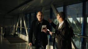2 люд в аэропорте идут вниз с прихожей в поисках приема на полете акции видеоматериалы
