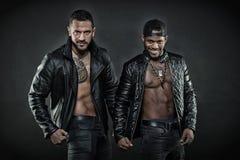 2 люд в кожаных куртках на черной предпосылке Зверский испанский человек с геометрической татуировкой Африканский человек с счаст Стоковое Фото