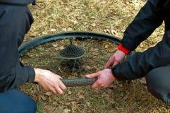 2 люд гранича колесо велосипеда, автошины велосипеда прокола, велосипед ремонта утомляют в поле Стоковое Фото