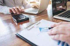 2 люд дела работая на столе офиса и обсуждая использующ Стоковое Изображение