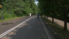 2 люд играют спорт в парке города Одно едет велосипед, другое бежит акции видеоматериалы