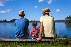 2 люд и малыш на озере стоковое изображение