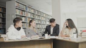 2 люд и 2 студента колледжа женщин смеясь промежутком времени подготавливая для экзаменов пока сидящ на таблице на университетско сток-видео