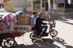 2 люд на электрической кресло-коляске с трейлером Стоковая Фотография