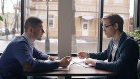 2 люд работают на светокопии, сидя на таблице в кофейне акции видеоматериалы